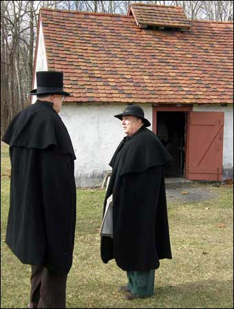 Hopewell Furnace, PA - Two colonial men talking outside of the blacksmith shop, Notice the clay tiles on the roof of the shop. When the shop caught on fire, some of the tiles needed replaced. 200 years later the same mold was found to make new tiles to replicate the old tiles<br>