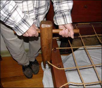 Bed Roping - An antique bed key is used to tighten the rope. In this photo, the bed key will be turned counterclockwise to tighten the second rope below the headboard.<br>